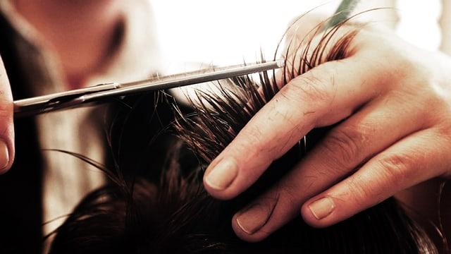 Coiffeuse schneidet mit einer Schere Haarspitzen ab.