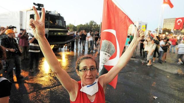 Eine Frau demonstriert friedlich vor einem gepanzerten Wasserwerfer.