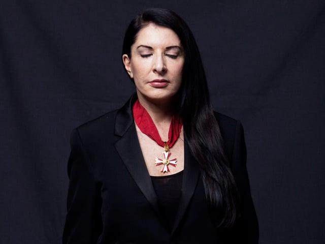 Das Bild zeigt eine dunkel gekleidete Frau vor dunklem Hintergrund, die die Augen schliesst und in meditativer Haltung weilt.