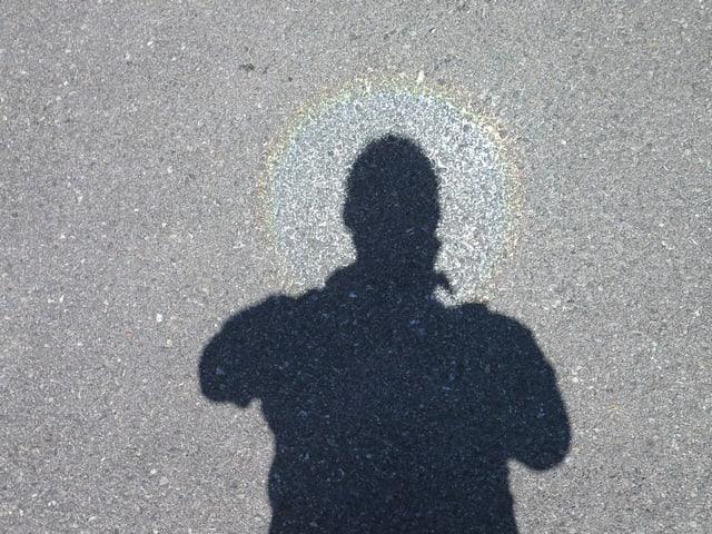 Asphalt, Schatten mit Lichtring um den Kopf.