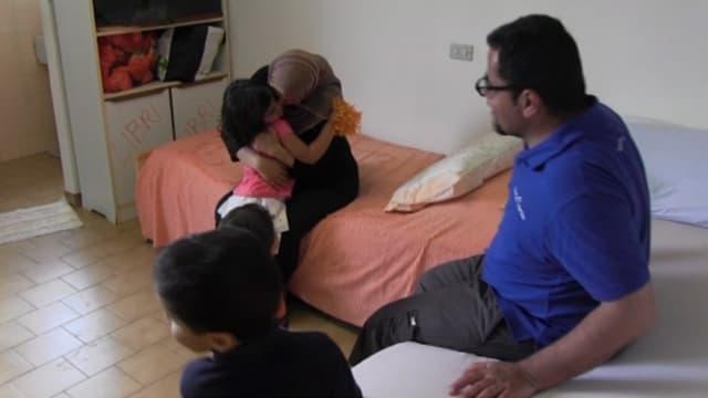 Die Familie sitz auf einem Bett, die Mutter umarmt ihre älteste Tochtger.