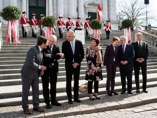 Bundesräte vor Treppe, auf der Tambouren stehen.