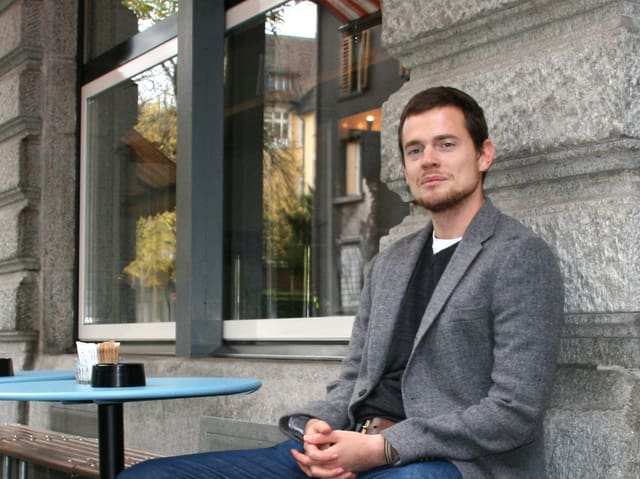 Ein junger Mann mit grauem Kittel sitzt vor einem Haus.