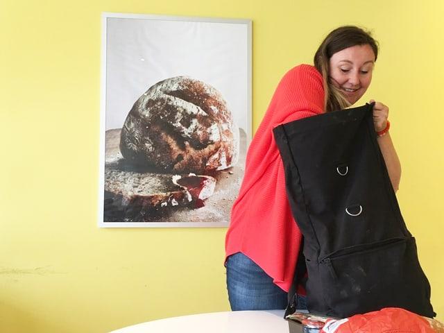 Christina Lang greift in ihren Rucksack.