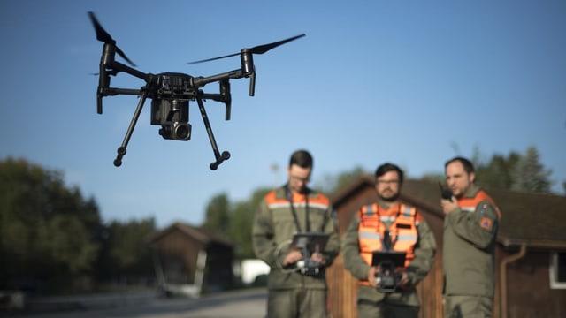 Ina drona e trais umens en unifurma da servetsch civil.