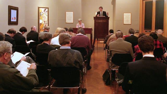 Ein Auktionator steht auf einem Podium, davor sitzen die Bieter.