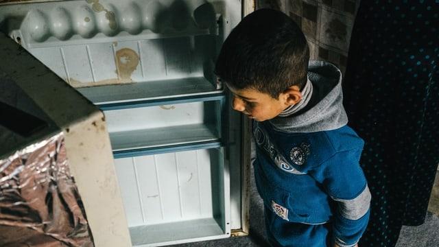 Junge schaut in leeren Kühlschrank.