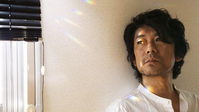Ein Mann im weissem Hemd, der an einer Wand lehnt. Er Blickt in Richtung Fenster.