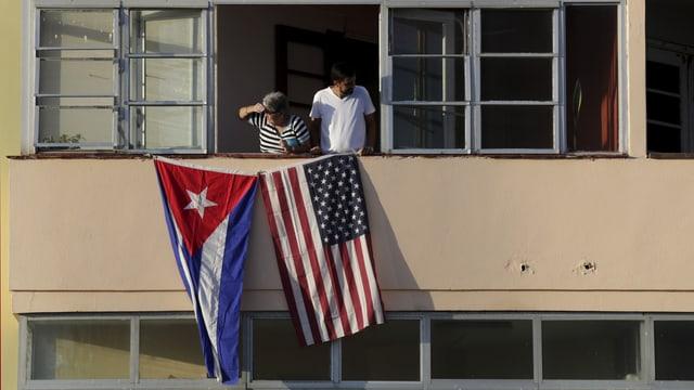 Eine kubanische und eine amerikanische Flagge an einem Haus, aus dem Fenster schauen zwei Personen.