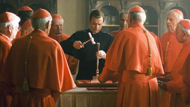 Ein Mann mit schwarzem Umhang zerstört mit einem Hammer einen Ring. Um ihn herum stehen Männer in roten Umhängen.