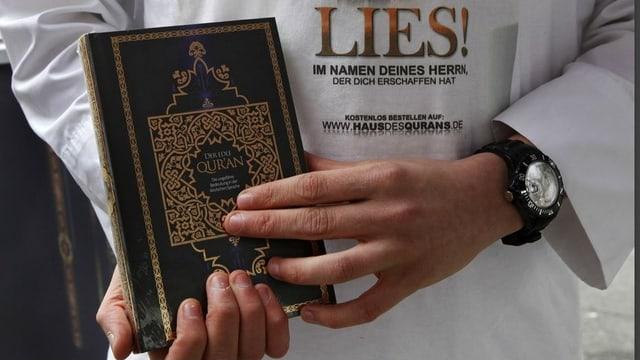 """Hände präsentieren einen Koran. Im Hintergruind sieht man das T-Shirt mirt der Aufschrift """"Lies!""""."""