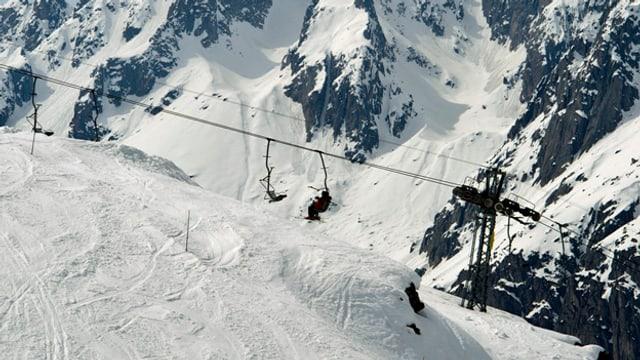Sessellift mit Skifahrer drauf.