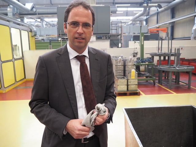 Jens Breu steht in der Werkhalle. Er trägt einen grauen Anzug, ein weisses Hemd und eine dunkelrote Krawatte. In der Hand hält er ein Metallteil. Er trägt eine Brille und hat dunkles, leicht schütteres Haar.