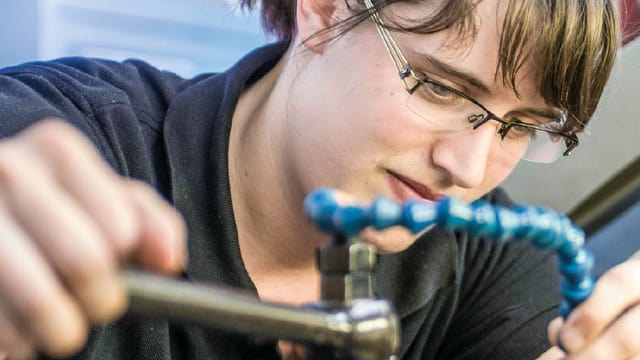 Eine Mechanikerin in Ausbildung zieht eine Schraube an.