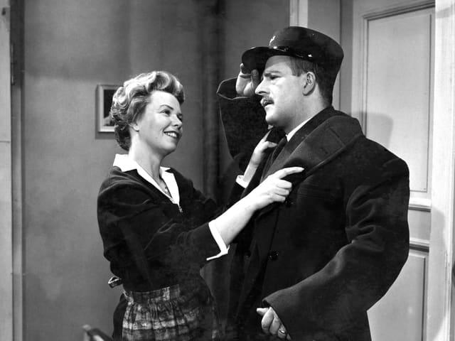 Eine Frau empfängt einen Mann an der Tür, sie lächelt und hält ihn am Jackett, während er sich an den Hut fasst.