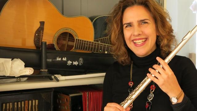 Eine Frau hält eine Querflöte - dahinter eine Gitarre.