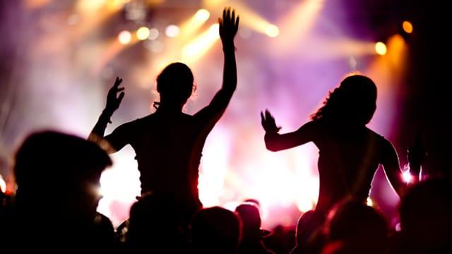 Publikum bei einem Festival. Zwei Frauen sitzen auf den Schulern von Zuschauern.