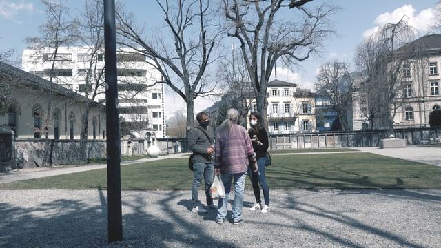 Drei Menschen stehen im Stadtpark Chur