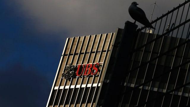Firmenlogo der UBS und rechts im Bild die Umrisse einer Taube auf einem Zaun.