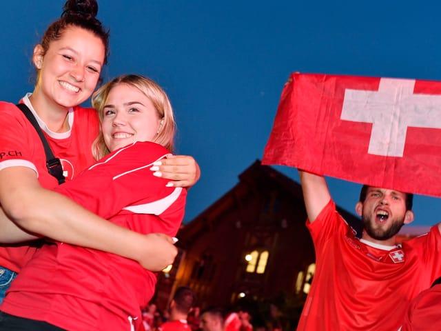 Fans mit Schweizer Fahne, die sich umarmen.