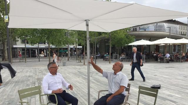Stadtingenieur Vilmar Krähenbühl und Stadtrat Filippo Leutenegger sitzen unter einem Sonnenschirm auf dem Sechseläutenplatz.