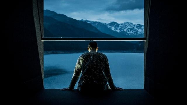 Ein Mann sitzt an einer grossen Luke und schaut aufs Wasser. Hinter ihm sind Berge.