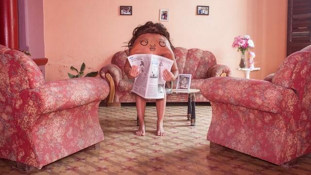 Ein Mann beugt sich im Wohnzimmer nach vorne, auf dem Rücken ein Gesicht gemalt. Er hat eine Zeitung in der Hand.