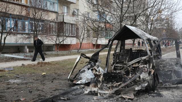 Ein ausgebranntes Autowrack steht auf einer Strasse in einem Wohnquartier