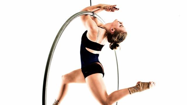 Artistin Nora Zoller zieht sich mit ihren Armen im Zirkusreif hoch und streckt das linke Bein grazil nach hinten.