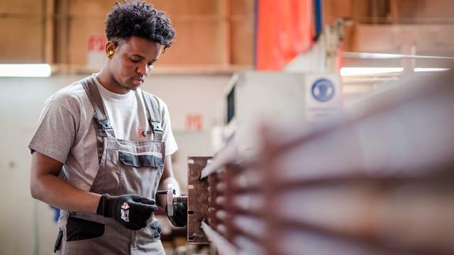 Ein junger Flüchtling arbeitet an einer Maschine.