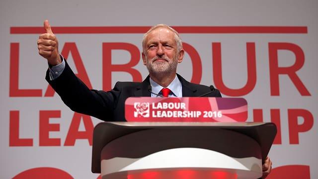 Corbyn steht hinter einem Stehpult und hält den Daumen hoch.