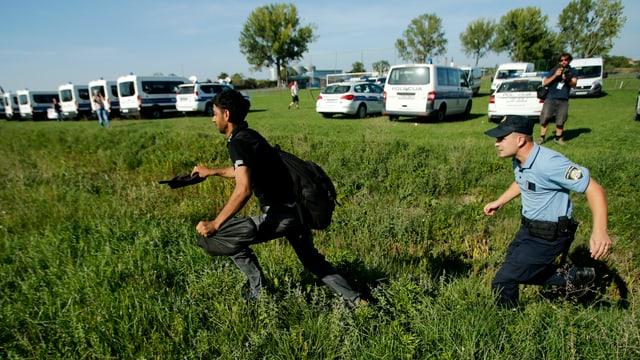Ein Flüchtling und ein Polizist rennen durchs Gras
