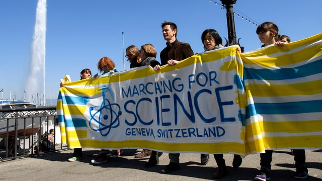 Purtret da persunas che tignan in grond placat «Marching for Science Geneva, Switzerland»