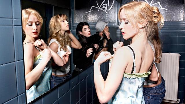 Vier junge Frauen stehen gemeinsam vor einem grossen Spiegel und machen sich zurecht: Sie zupfen an den Trägern ihres Oberteils, stecken Ohrringe an oder frisieren sich.