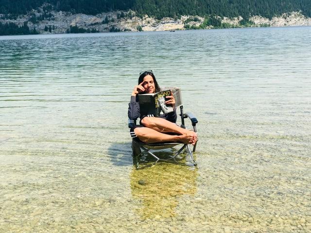Annette König sitzt auf einem Klappstuhl im Lac de Joux. Dazu liest sie «Blond» von Joyce Carol Oates
