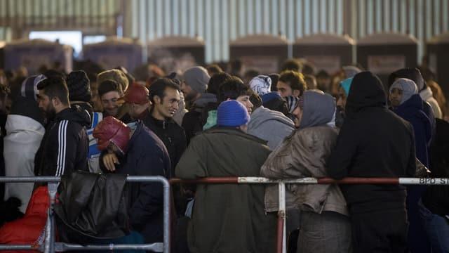 Flüchtlinge stehen dichtgedrängt in einer Schlange.