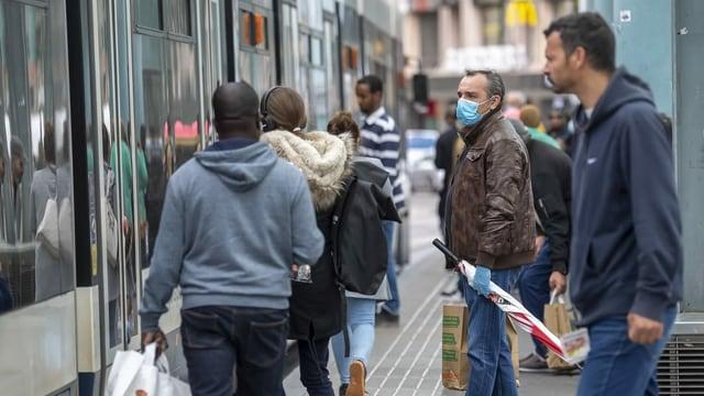 Menschen an einer Bushaltestelle, ein Mann trägt eine Maske.