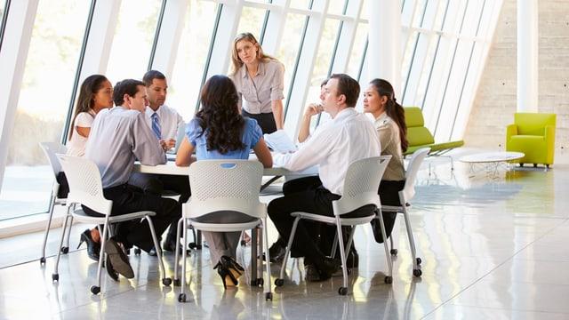 Businessleute sitzen um einen Tisch. Die Chefin steht.