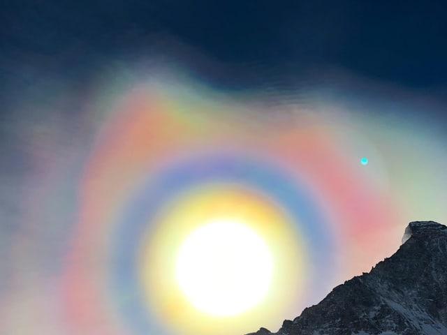 Rund um die Sonne, sie steht neben dem Matterhorn am Himmel, hat sich scheibenförmig eine sogenannte Korona gebildet. Sie schillert in gelb,gold, blau, grün und rosarot.