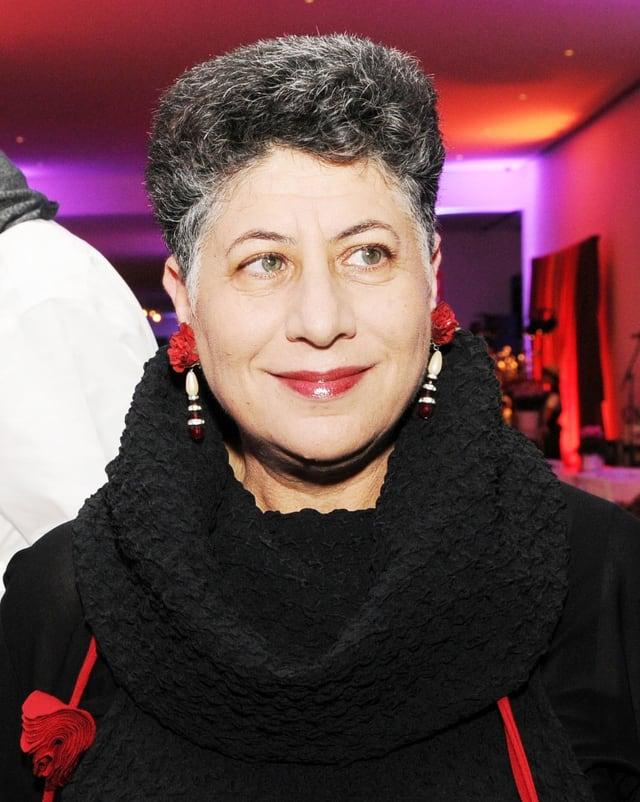 Eine Frau mit kurzen grauen Haaren und lächelt.