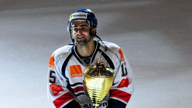 Ein Eishockeyspieler mit einem Pokal.