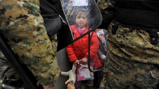 Ein Mädchen steht zwischen zwei Soldaten