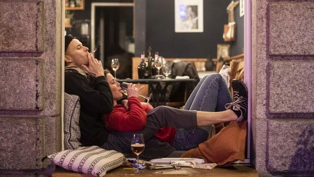 Mann und Frau sitzen im Fenster einer Bar und rauchen und trinken.