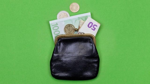 Ein kleiner Geldbeutel, aus dem Geldscheine und Münzen herausragen.