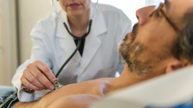 Eine Ärztin hört einen Patienten mit einem Stethoskop ab.