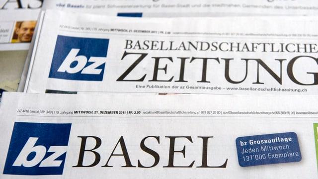 Foto von einer Ausgabe der bz Basel, darunter liegt eine Ausgabe der Basellandschaftlichen Zeitung.