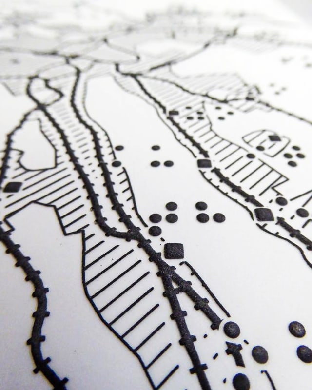 Landkarte mit Brailleschrift, Punkten und schraffierten Flächen.