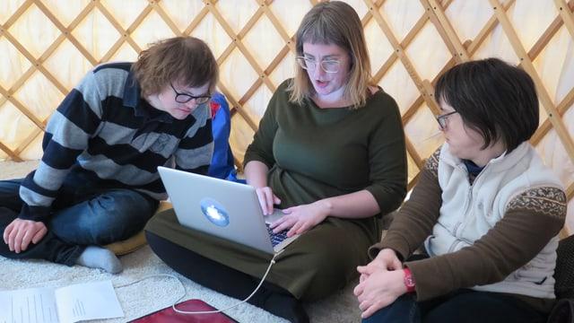 Ein Mann und eine Frau blicken einer Frau in ihrer Mitte über die Schulter, die etwas auf einem Computer schreibt