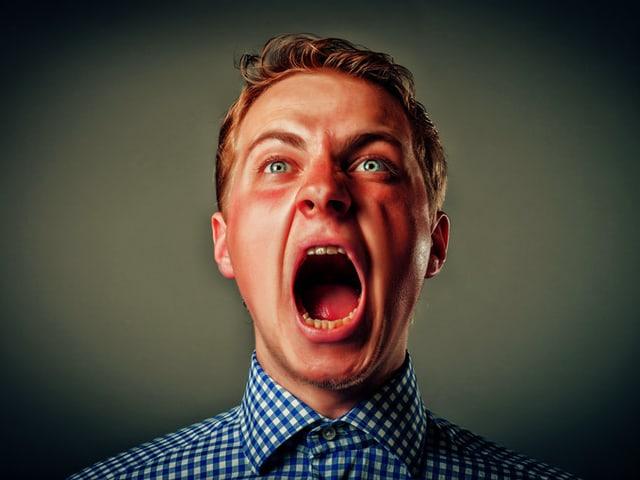 Mann mit hochrotem Kopf schreit vor grünem Hintergrund