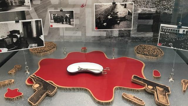 Vitrine im Basler Polizeimuseum mit Fotos und Karton-Pistolen.